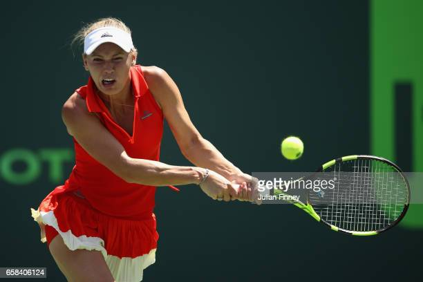 Caroline Wozniacki of Denmark plays a backhand in her match against Garbine Muguruza of Spain at Crandon Park Tennis Center on March 27 2017 in Key...