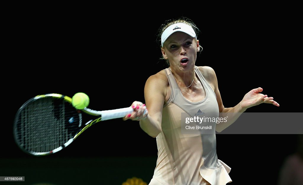 Caroline Wozniacki of Denmark plays a forehand against Maria Sharapova of Russia in their round robin match during the BNP Paribas WTA Finals at Singapore Sports Hub on October 21, 2014 in Singapore.