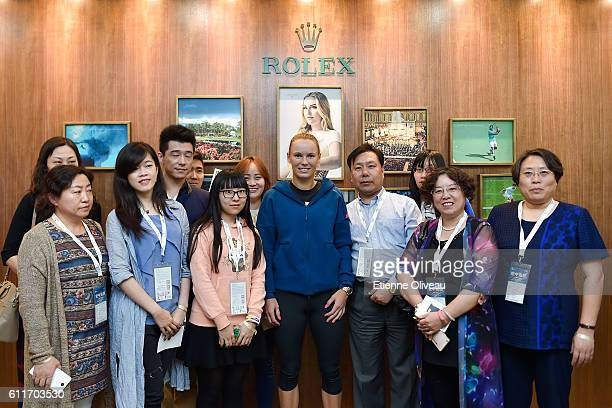 Caroline Wozniacki of Denmark poses for a picture with staff members at the Rolex Skybox on day 1 of the 2016 China Open at the National Tennis...