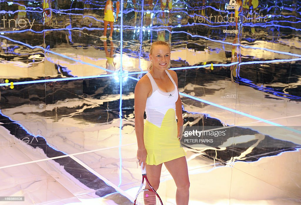 Caroline Wozniacki of Denmark poses in a new adidas outfit by British designer Stella McCartney at a launch on a tennis court made entirely of mirrors in a studo in Melbourne on January 13, 2013, ahead of the 2013 Australian Open tennis tournament. AFP PHOTO / Peter PARKS IMAGE