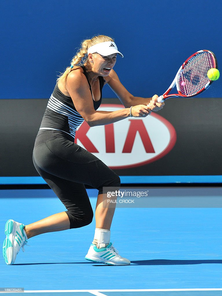 Caroline Wozniacki of Denmark reacts as she hits a return during a practice session for the upcoming Australian Open tennis tournament in Melbourne on January 10, 2013. The first Grand Slam tennis tournament of the year is set to run from January 14 to 27. AFP PHOTO / Paul CROCK IMAGE