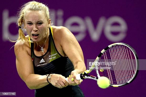Caroline Wozniacki of Denmark rerturns a shot to Vera Zvonareva of Russia during the semifinals on day five of the WTA Championships at the Khalifa...