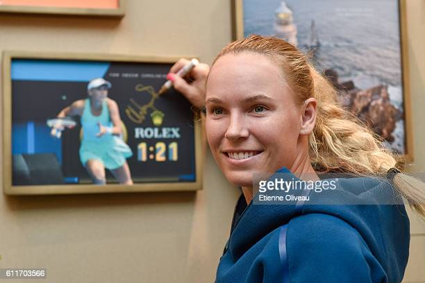 Caroline Wozniacki of Denmark signs an autograph on a picture at the Rolex Skybox on day 1 of the 2016 China Open at the National Tennis Centre on...