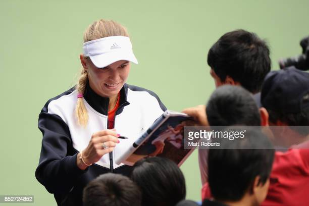 Caroline Wozniacki of Denmark signs autographs for fans after defeating Anastasia Pavlyuchenkova of Russia in the women's singles final match on day...