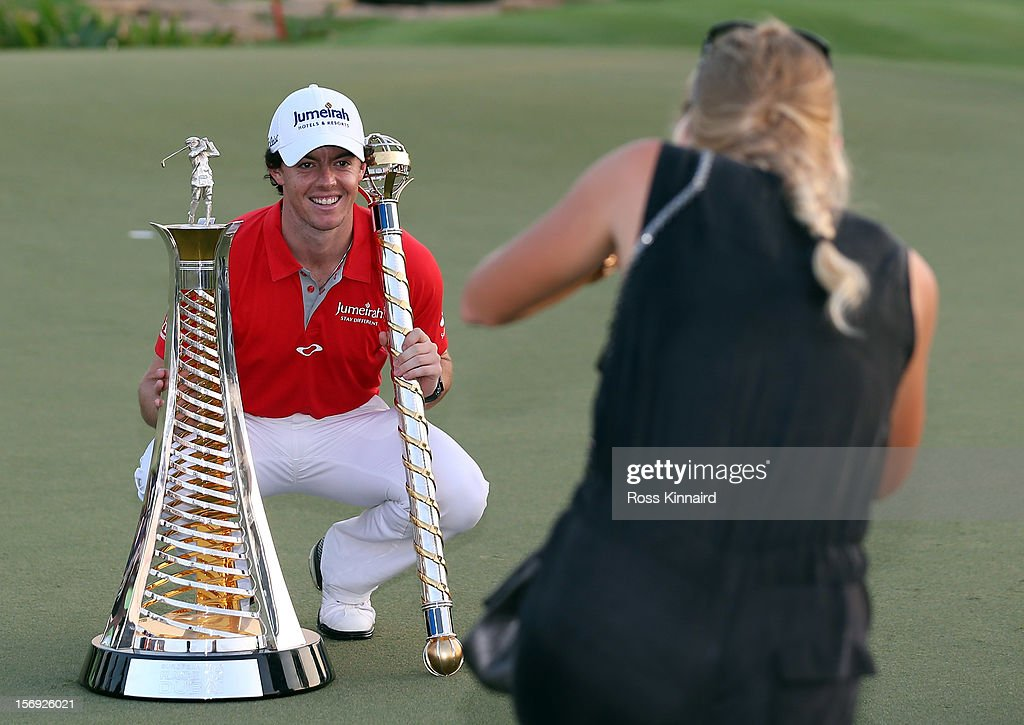 Caroline Wozniacki of Denmark takes a picture of her boy friend, Rory McIlroy of Northern Ireland with the DP World Tour Championship and The Race to Dubai trophy on the 18th green during the final roung of the DP World Tour Championship on the Earth Course at Jumeirah Golf Estates on November 25, 2012 in Dubai, United Arab Emirates.
