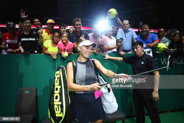Caroline Wozniacki of Denmark takes a selfie with fans as she celebrates victory in her singles match against Simona Halep of Romania during day 4 of...