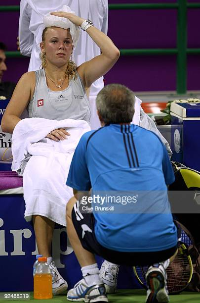 Caroline Wozniacki of Denmark talks to her father and coach Piotr as she cools down with an ice pack on top of her head in their round robin match...