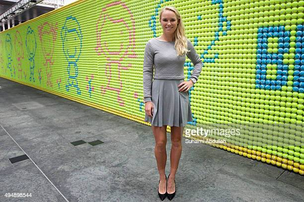 Caroline Wozniacki poses for a photo after unveiling the largest tennis ball mosaic by Mundipharma at Asia Square on October 30 2015 in Singapore The...