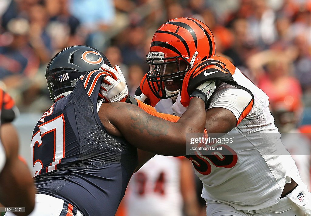 Carolos Dunlap #96 of the Cincinnati Bengals rushes against Jodan Mills #67 of the Chicago Bears at Soldier Field on September 8, 2013 in Chicago, Illinois. The Bears defeated the Bengals 24-21.