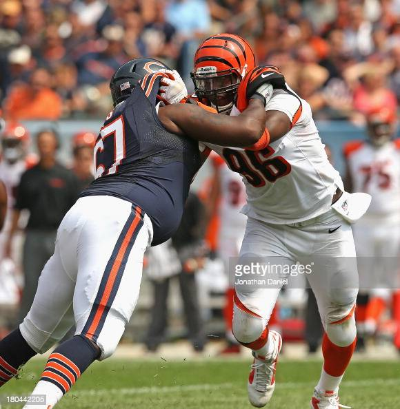 Carolos Dunlap of the Cincinnati Bengals rushes against Jodan Mills of the Chicago Bears at Soldier Field on September 8 2013 in Chicago Illinois The...