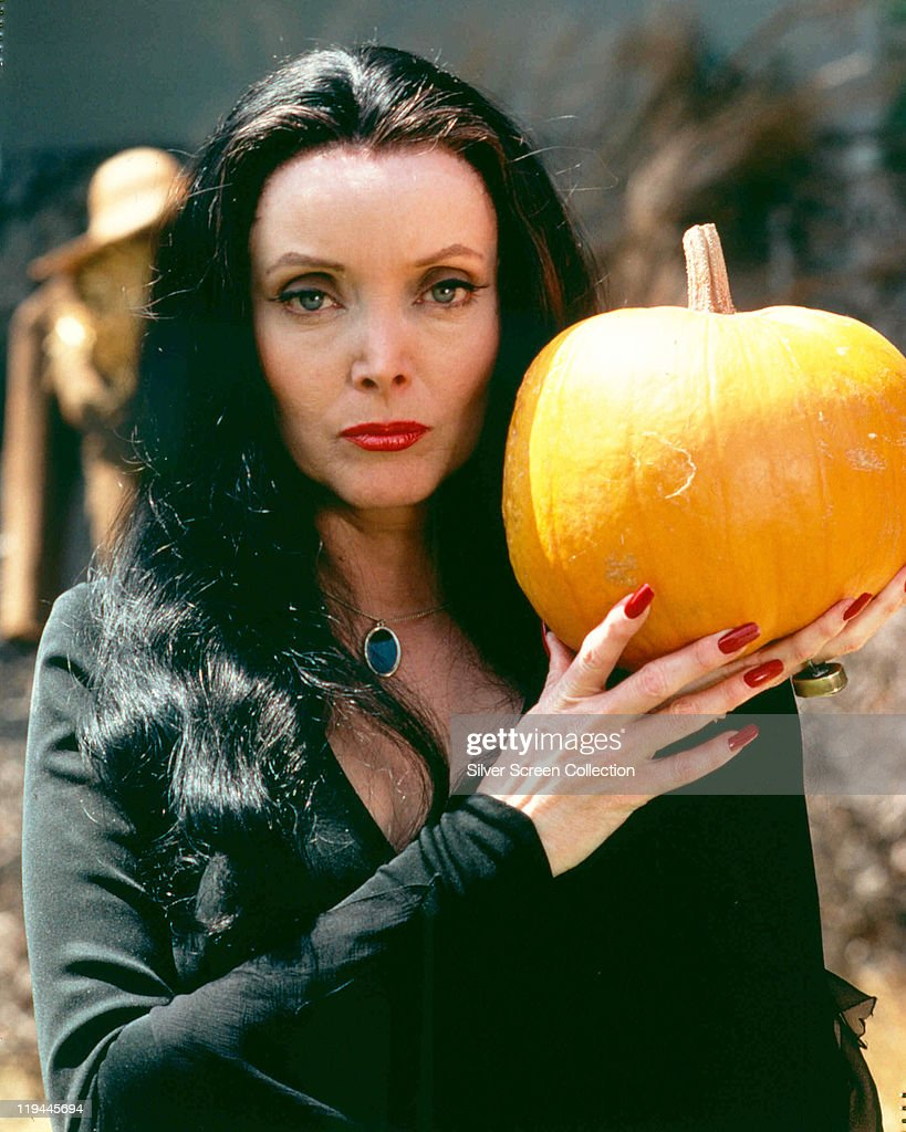 Carolyn Jones [1930-1983), US actress, in costume and holding a pumpkin in a publicity portrait issued for the US television series, 'The Addams Family', USA, circa 1965. The sitcom starred Jones as 'Morticia Frump Addams'.