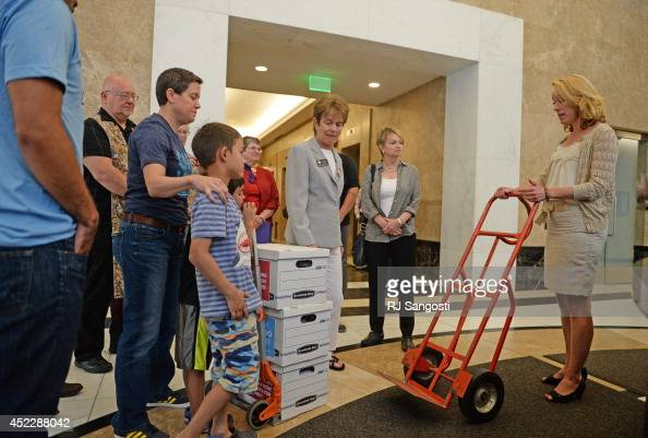Carolyn Tyler right from Colorado Attorney General John Suthers' office brings a handcart to pick up boxes of petition delivered by group of...