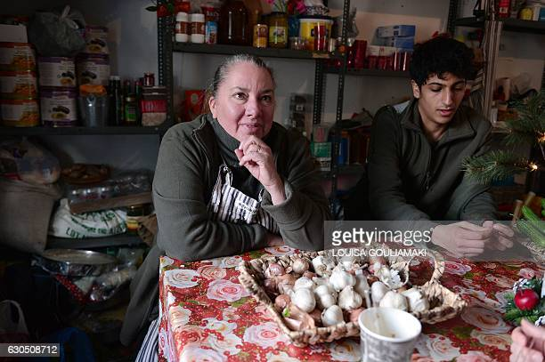 Carolynn Rockafellow an American former investment banker talks with Syrian volunteer helping in the kitchen of 'cafe Rits' in Ritsona refugee camp...