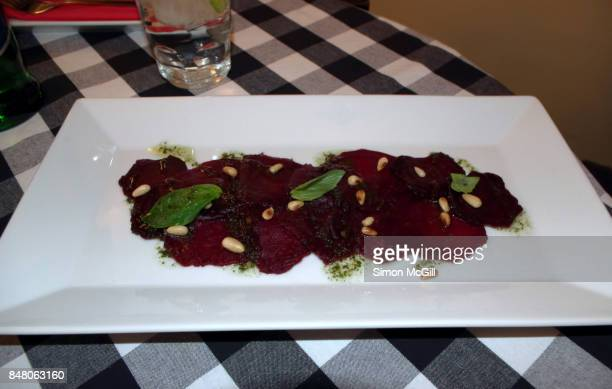 Carpaccio of red beetroot with roasted pine nuts and basil oil