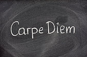 Enjoy life before it's too late, existential cautionary Latin phrase, Carpe Diem, a quote from Horace, handwritten with white chalk on blackboard.