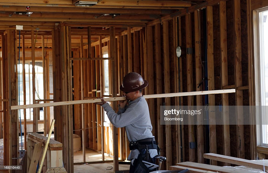 A carpenter carries lumber at a home under construction at the Hovnanian Enterprises Inc.'s Four Seasons housing development in Beaumont, California, U.S., on Monday, March 4, 2013. Hovnanian Enterprises Inc., the best-performing U.S. homebuilder stock in the past 12 months, reported a narrower loss for its fiscal first quarter as sales and orders increased amid a housing rebound. Photographer: Patrick T. Fallon/Bloomberg via Getty Images