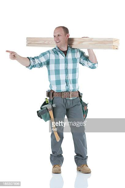 Carpenter carrying wooden planks
