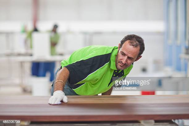 Carpenter checking quality of wood in workshop