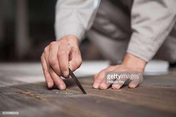 Carpenter checking quality of wood plank in factory, Jiangsu, China