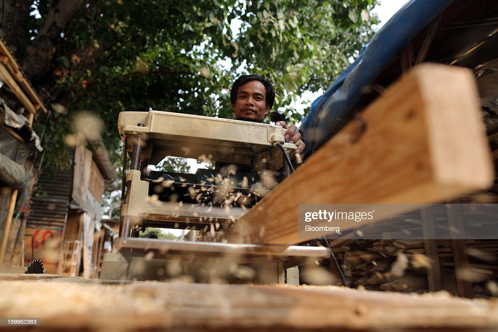 A carpenter cuts wood on a table saw at a workshop in Bangkok, Thailand, on Wednesday, Jan. 23, 2013. Prime Minister Yingluck Shinawatra's government last month approved a new round of increases in the daily minimum wage to 300 baht ($9.8) from the beginning of this year, after a similar raise in April in seven provinces including Bangkok. Photographer: Dario Pignatelli/Bloomberg via Getty Images
