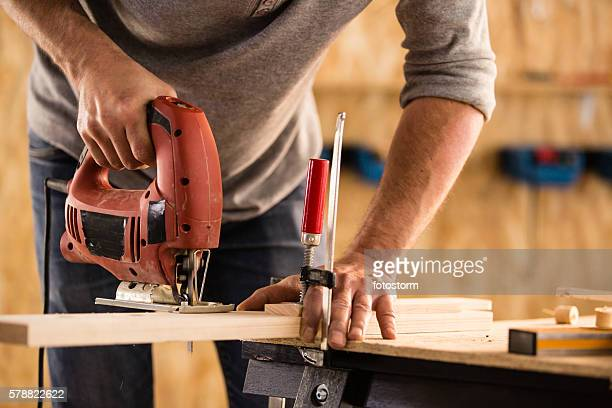 Carpenter cutting a wood using jigsaw cutter