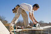 Carpenter cutting plank with a circular saw