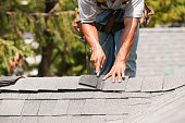 Carpenter cutting shingles on roof peak