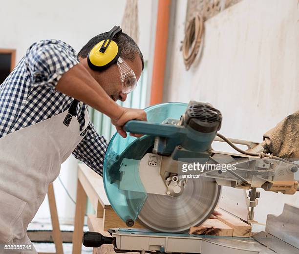 Carpenter cutting wood at the carpentry