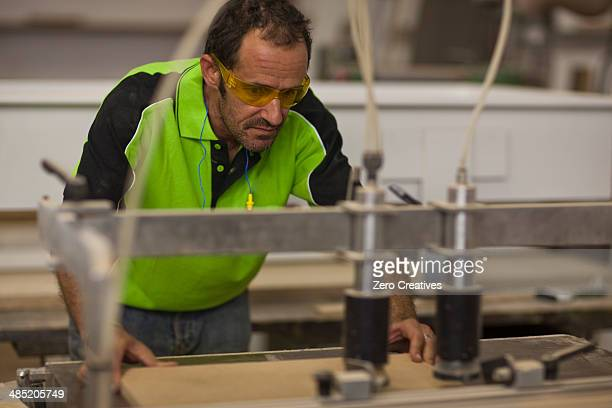 Carpenter cutting wood on table saw in workshop