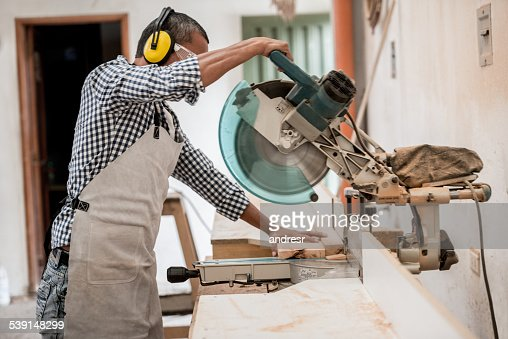 Carpenter cutting wood with a circular saw