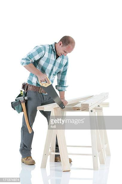 Carpenter cutting wooden plank with a saw