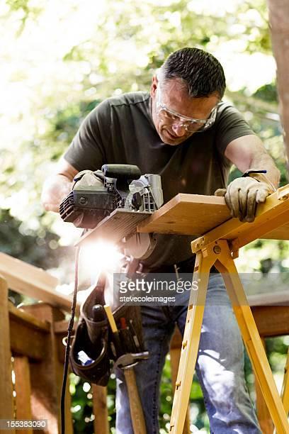 Carpentiere taglio asse di legno con sega circolare.