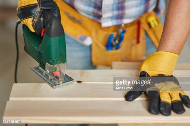 Carpenter doing woodwork by sawing wood. Debica, Poland