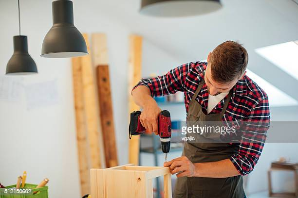 Carpenter drilling wooden plank