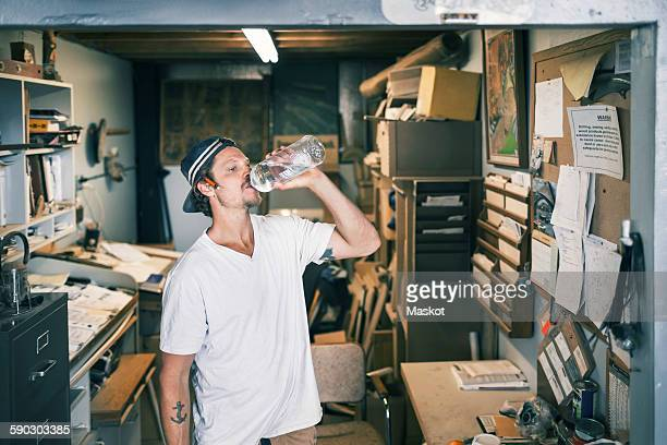 Carpenter drinking water in workshop