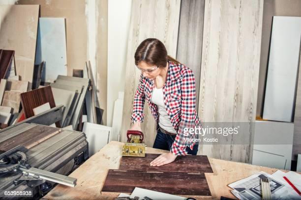 Carpenter girl working in a carpentry workshop