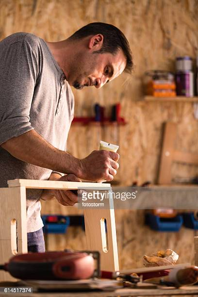 Carpenter gluing wood product in workshop