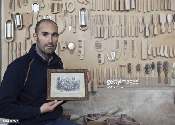 Carpenter holding old photograph in workshop