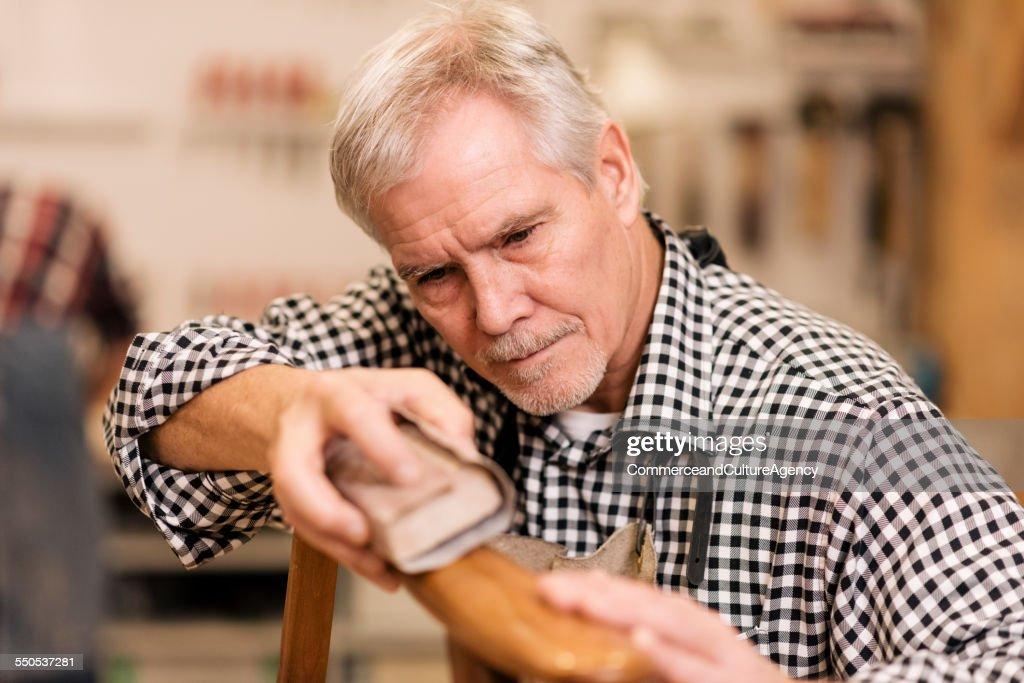 carpenter in wood workshop sanding a chair