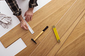 Carpenter installing a wooden flooring and measuring with a precision ruler, top view