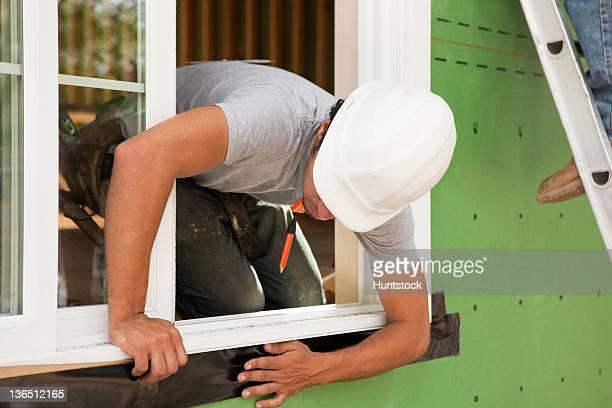 Carpenter installing flashing around window frame
