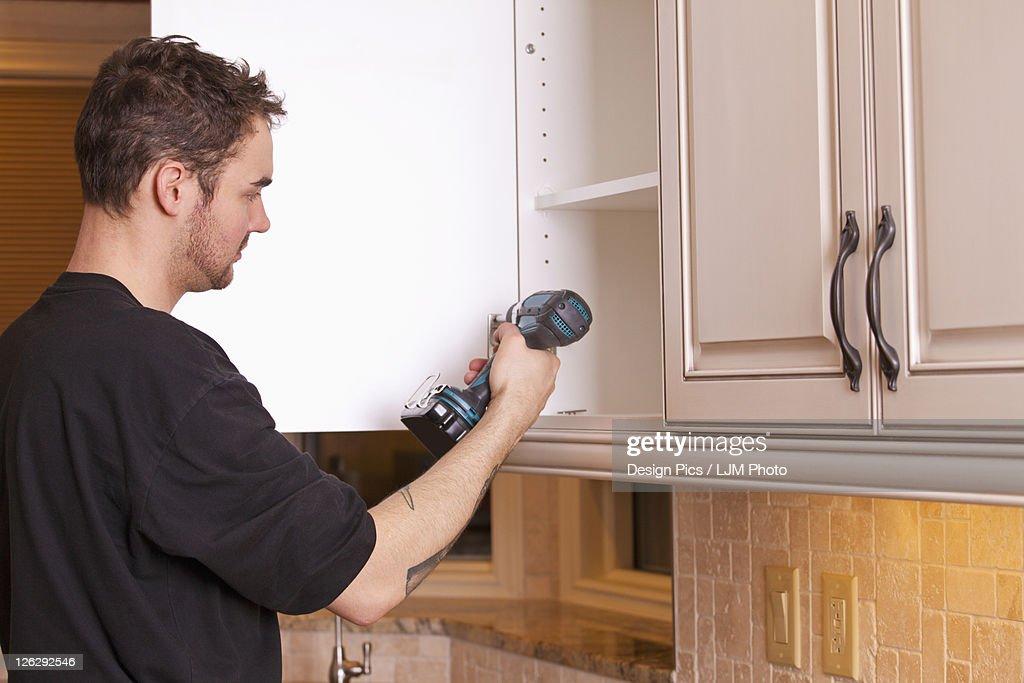 Carpenter Installing New Kitchen Cabinets Stock Photo