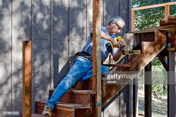 Carpenter installing wooden stairs outdoors