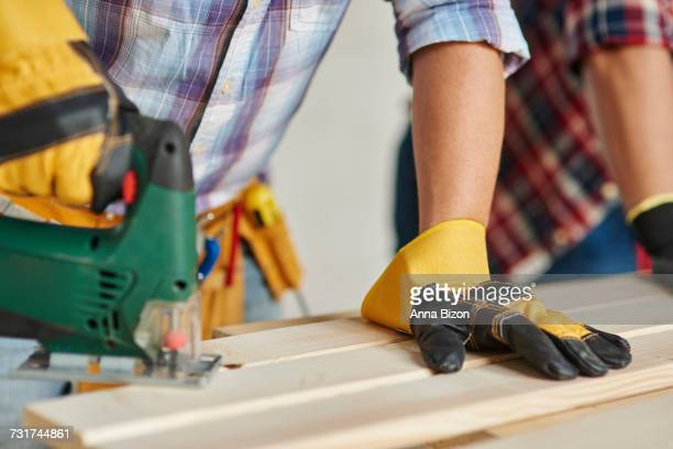 Carpenter is sawing wooden planks by electric saw. Debica, Poland