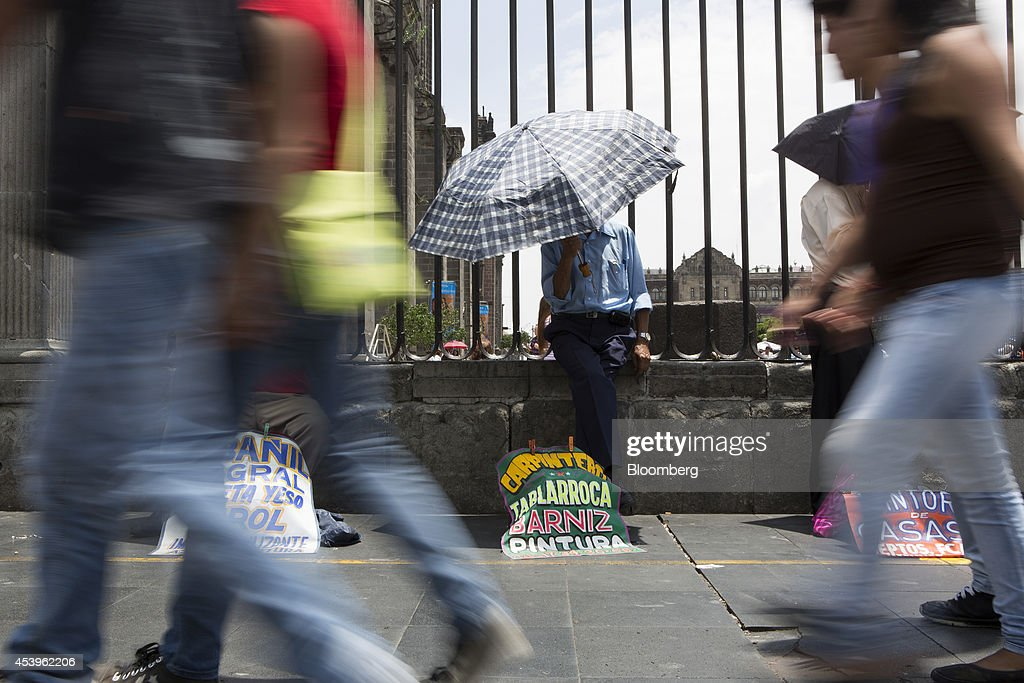 A carpenter looking for work stands with an umbrella behind a sign advertising his services in the traditional main plaza known as the Zocalo in Mexico City, Mexico, on Thursday, Aug. 21, 2014. Mexican consumer prices rose more than analysts expected in the first half of August and the unemployment rate rose to 5.47 percent in July compared with 4.8 percent in June. Photographer: Susana Gonzalez/Bloomberg via Getty Images