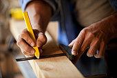 Carpenter Marking a Wooden Plank