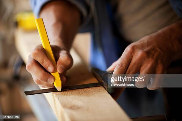 Carpenter Marking a Wooden Plank