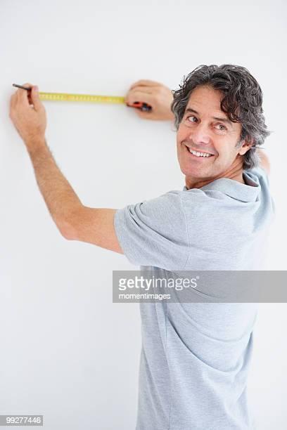 Carpenter marking straight line on wall
