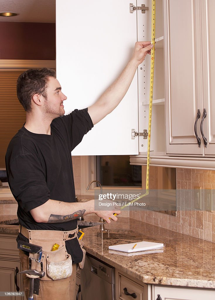 Carpenter measuring and installing new kitchen cabinets for Carpenter for kitchen cabinets