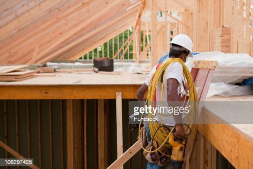 Carpenter moving tools down ladder at end of day to go home : Stock Photo